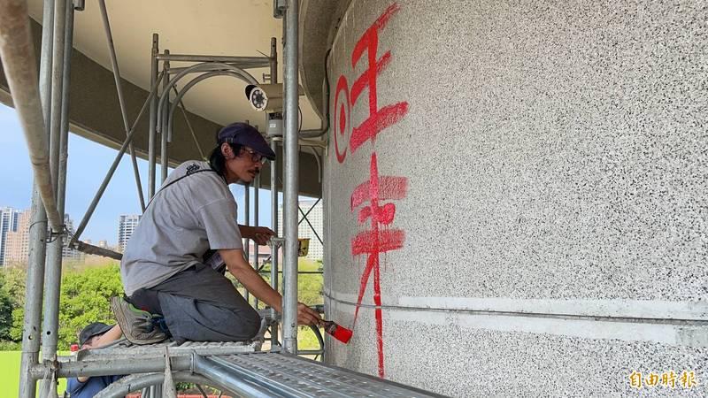 藝術家李俊陽在開工儀式中,於將創作的壁面寫下「旺來今招」,期許創作順利。(記者許麗娟攝)