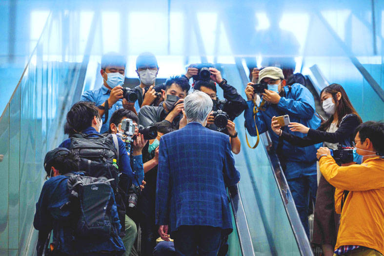 Former Hong Kong legislator Martin Lee, center, facing away, is surrounded by journalists as he takes an escalator after his arrival at a court in Hong Kong yesterday. Photo: AFP
