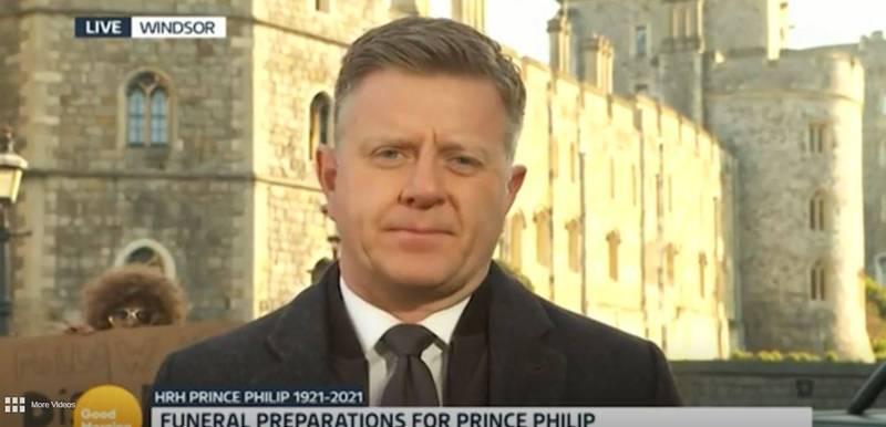 英國「獨立電視台」播出晨間電視節目《早安英國》時,竟有個男子(左)在英國王室新聞編輯希普(右)面對鏡頭說話時,趁機站在他身後舉出宣傳板。(圖擷取自ITV影片)