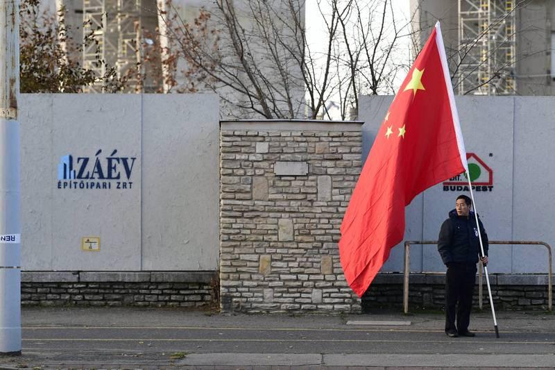 男子手持中國國旗在匈牙利街頭。(歐新社)