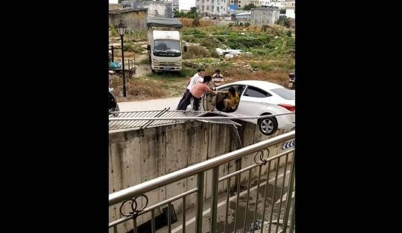 中國廣西貴港一名女子倒車意外,半截車身懸在半空中。(圖擷取自Youtube veMak)