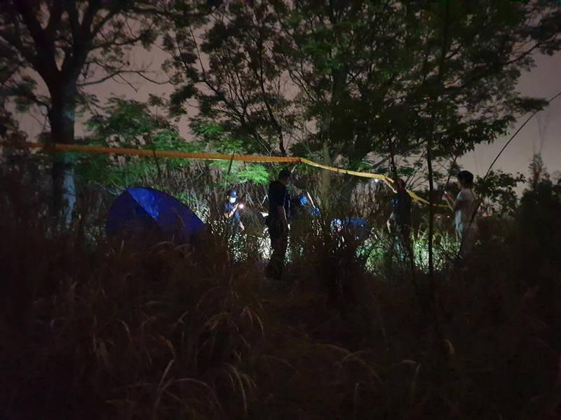 外籍移工在草屯鎮植物公園圍欄外滯洪池後方草叢中要撿空拍機,卻意外發現乾屍,警方封鎖現場初勘。(圖由民眾提供)