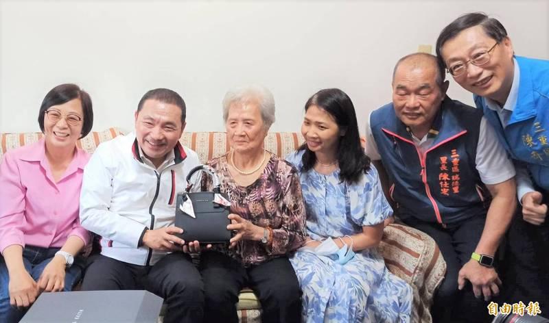 新北市長侯友宜(左二)今天拜訪新北市模範母親代表的86歲陳吳玉鳳(左三),並送上手提包祝賀她母親節快樂。(記者陳心瑜攝)