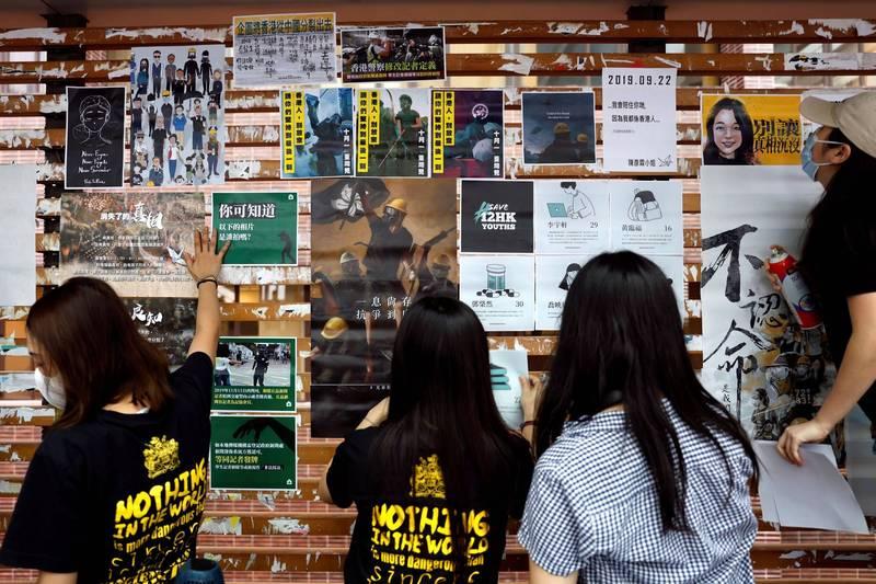 港大學生會日前抗議校方配合辦理所謂「國安教育日」,中官媒特別刊文痛批學生會。圗為去年港大學生在校園連儂牆上張貼民主標語。(路透)