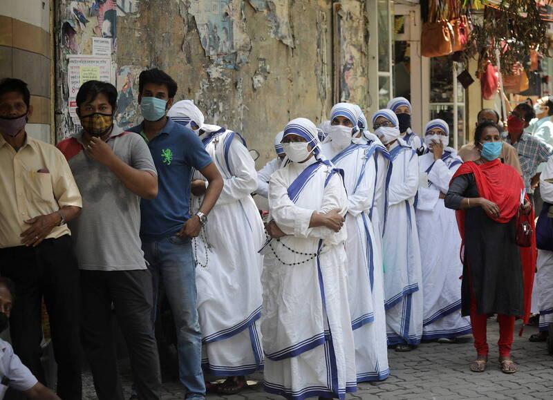 印度單日確診病例和死亡人數在週一雙雙創新高。圖為印度民眾排隊等候檢測。(歐新社)