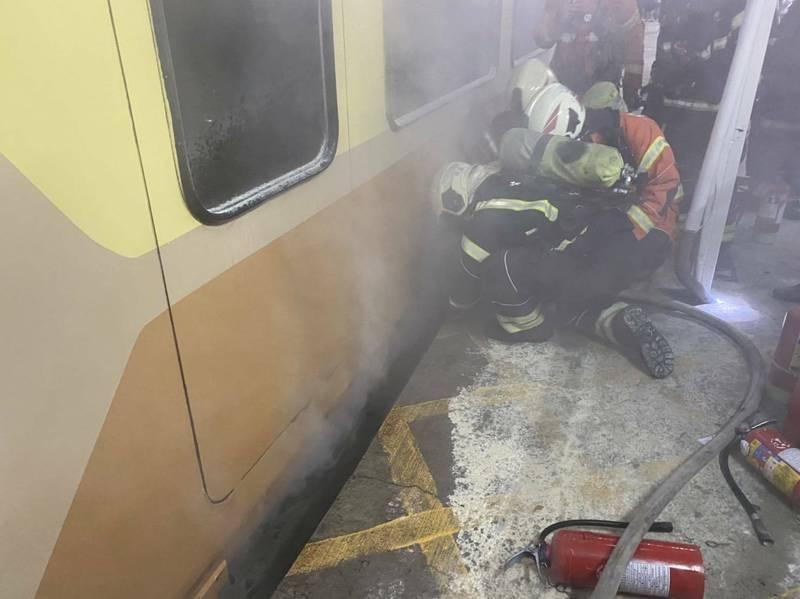 今年4月11日,台鐵EMU300型自強號停靠中壢站月台時,瀰漫燒焦味,消防隊出水降溫。(資料照,記者李容萍翻攝)