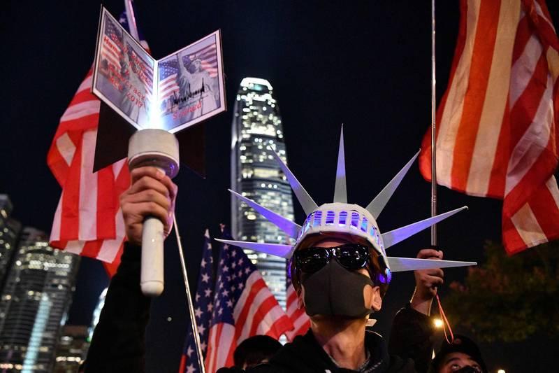美國前總統川普在2019年11月27日簽署《香港人權與民主法》後,香港民眾上街慶賀。(法新社檔案照)