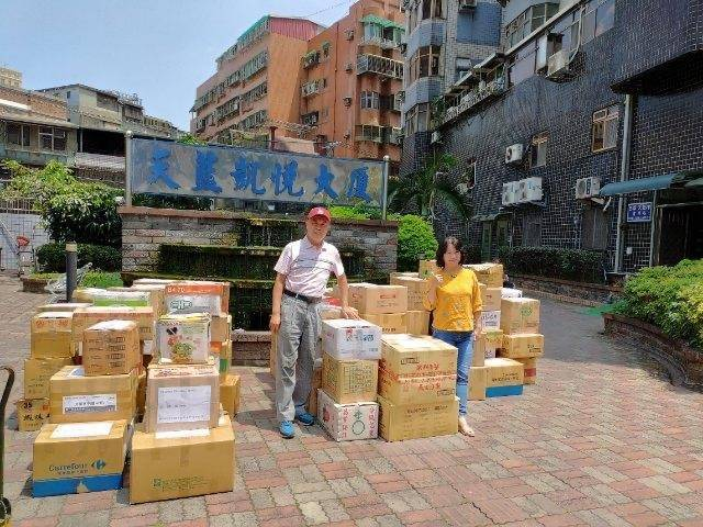 李聰任(左)與太太林淑瑤(右)合力將書籍裝箱準備寄出。(金門縣政府提供)