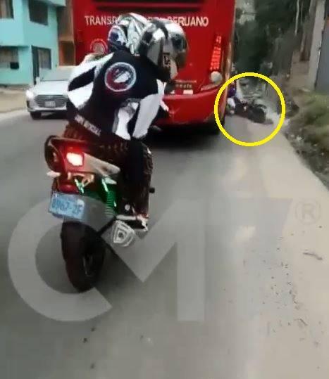 秘魯一名機車騎士(黃框處),想從紅色巴士的右側超車,但卻失去平衡遭輾入後輪慘死。(圖翻攝自Portalcm7官網)
