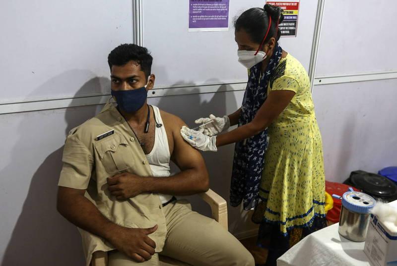 印度政府宣布,從5月1日起將允許所有18歲以上成人接種武肺疫苗。圖為一名警察於印度孟買施打武肺疫苗。(歐新社)