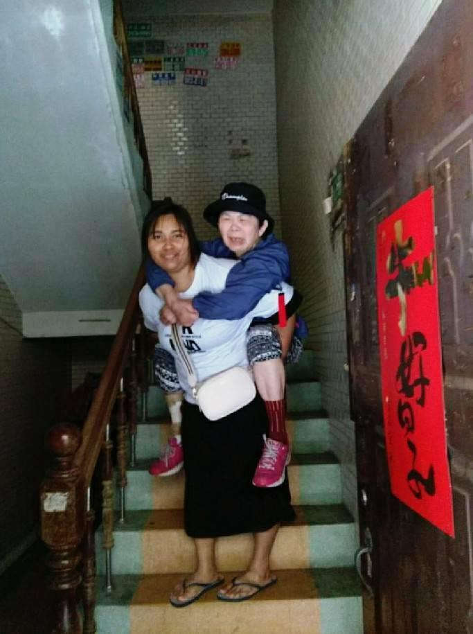 來自印尼的移工安妮(JARIANI),照顧中風的林阿嬤,每天揹著她上下3層樓到醫院復健。(圖由新北市政府勞工局提供)