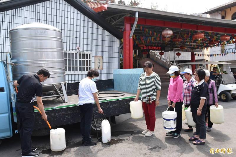 水情吃緊,自來水公司斗六服務所今天在斗六檨仔坑社區辦理無水體驗日,民眾拿水桶提水回家使用。(記者黃淑莉攝)