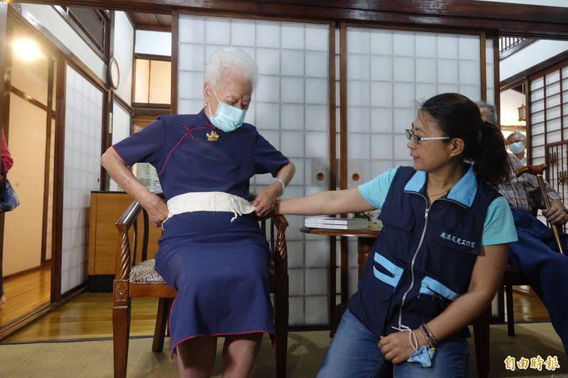一甲子前的肚臍保護棉布怎麼用?由103歲產婆黃蔡寬(圖左)來示範。(記者劉曉欣攝)