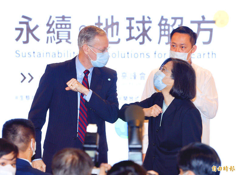 American Institute in Taiwan (AIT) Director Brent Christensen, left, gives President Tsai Ing-wen an elbow bump at a seminar to mark Earth Day hosted by the AIT in Taipei yesterday. Photo: Peter Lo, Taipei Times