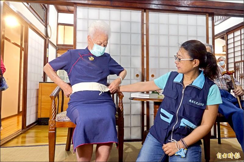 黃蔡寬(左)示範使用一甲子前的肚臍保護棉布。 (記者劉曉欣攝)