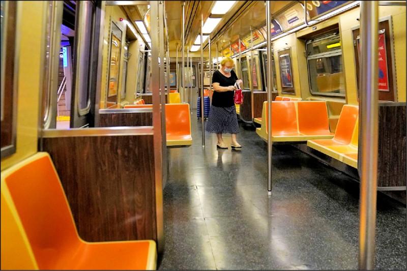2020年6月25日,一名女子獨自站在空無一人的紐約市地鐵車廂內。 (路透檔案照)
