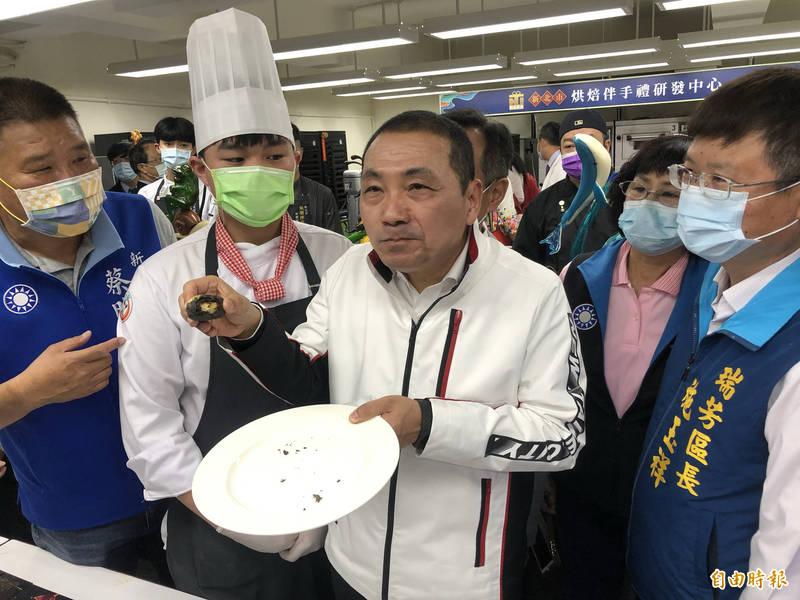 侯友宜試吃學生設計的「礦金餅」。(記者周湘芸攝)