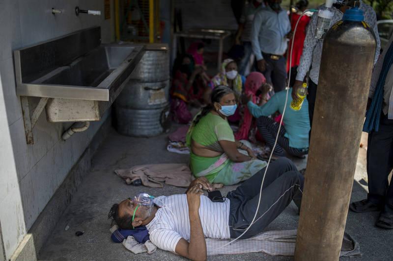 全球疫情持續爆發,近期印度確診病例爆增,醫療體系已無法負荷,民眾甚至被迫在教堂外臥地接受供氧。(美聯社)