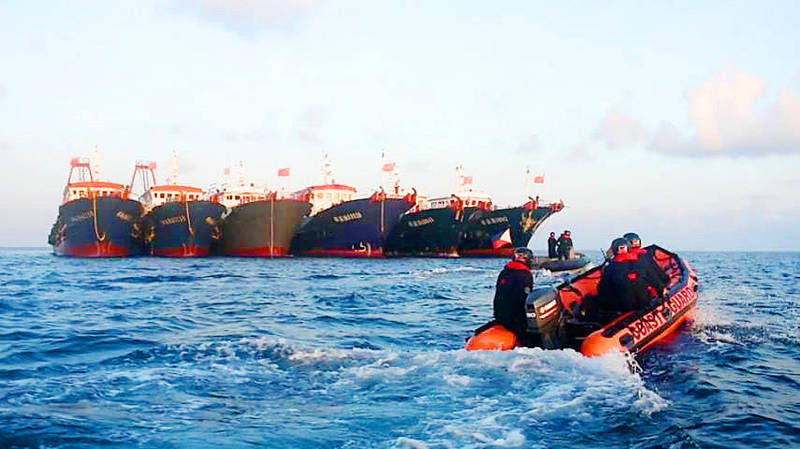 Philippine coast guard personnel aboard rubber boats sail past Chinese vessels near Whitsun Reef on April 14. Photo: EPA-EFE