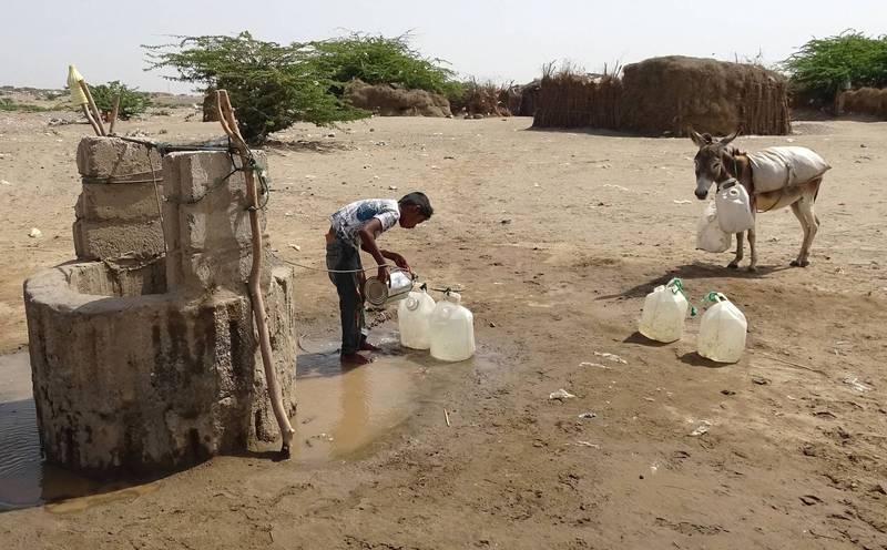 科學家指出,由於全球暖化和人類過度使用,全球多達20%的地下水井將面臨乾涸風險。圖為葉門西部戰火肆虐的荷台達省,1名男孩將取自水井的水裝進塑膠桶裡。(法新社)