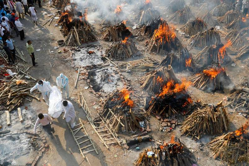 印度武漢肺炎疫情惡化,新德里這處火化病逝者的遺體只能堆起木柴與乾草路天焚燒。(路透)