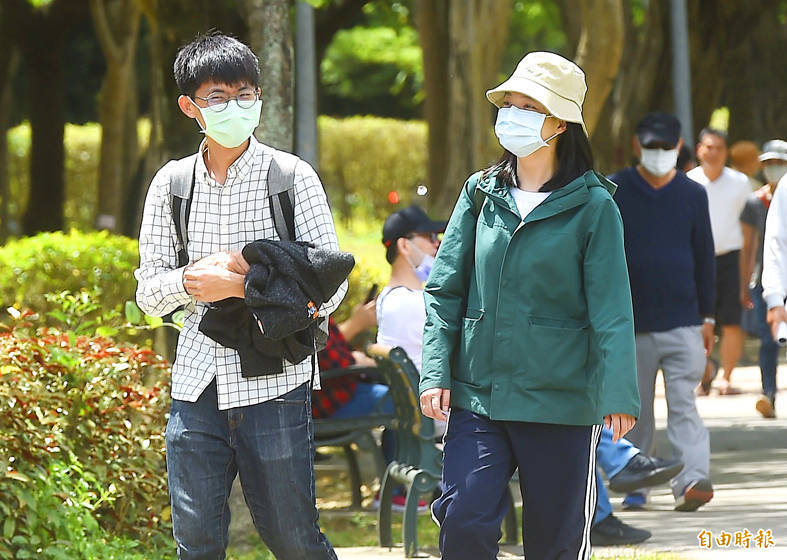 People wearing masks on Saturday walk along a path in Daan Forest Park, which is near the Taipei Grand Mosque in Taipei's Daan District. Photo: Chien Jung-fong, Taipei Times