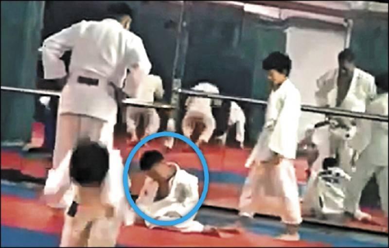 7歲男童(藍圈處)學柔道,被學長、教練摔來摔去,孩子禁不起側摔與過肩摔,腦部受創頹跪,並當場嘔吐昏迷。(家屬提供)