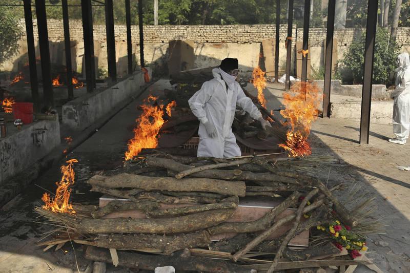印度疫情失控,首都新德里的火葬場傳出已沒有空位,當地官員試圖找尋其他地方處理遺體。圖為印度一名男子在指定火葬場火化家人。(美聯社)