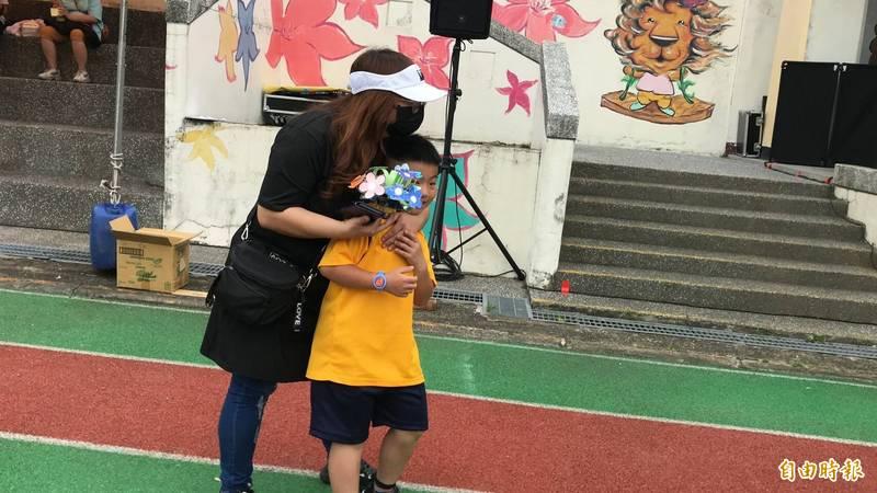 收到兒子的手做花束,1個媽媽一把攬住自家寶貝,用溫暖的懷抱給他回饋。(記者黃美珠攝)