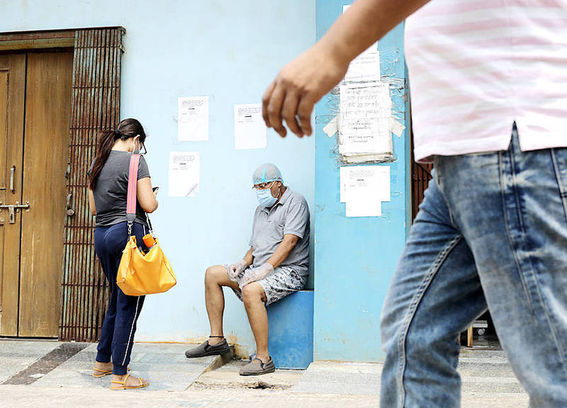 A suspected COVID-19 patient, sitting, waits to be admitted at a hospital in Kolkata, India, yesterday. Photo: EPA-EFE