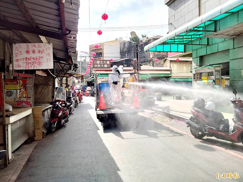 Environmental protection workers sanitize a street in Yunlin County's Beigang Township yesterday after a quarantine hotel worker who tested positive for COVID-19 on Friday visited Beigang on Sunday last week. Photo copied by Lin Kuo-hsien, Taipei Times