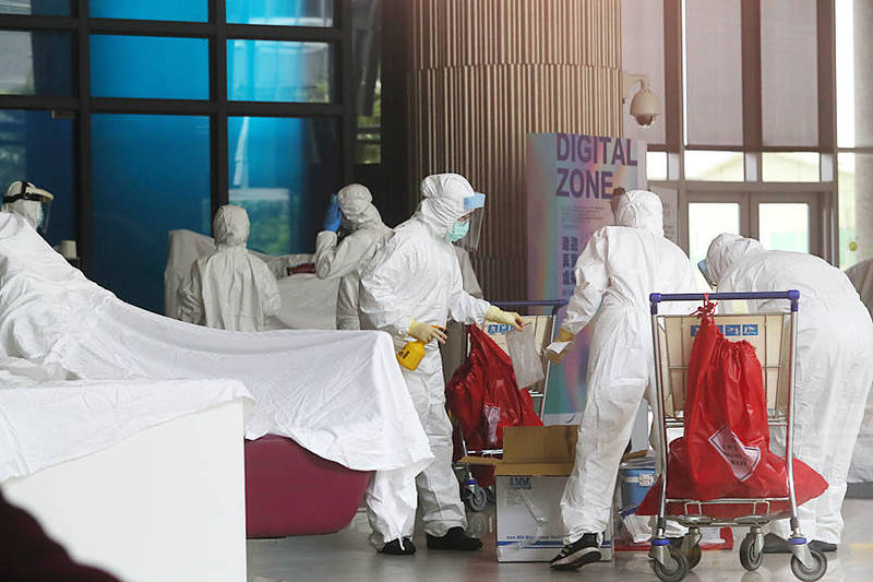 Workers wearing medical coveralls collect samples from the Novotel Taipei Taoyuan International Airport quarantine hotel yesterday as they investigate a cluster of COVID-19 infections connected to the hotel. Photo: CNA