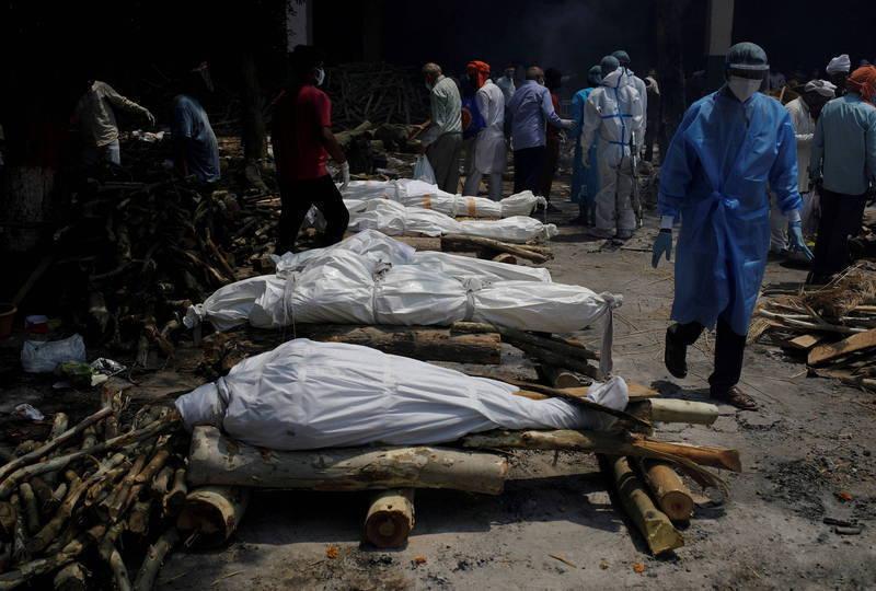 印度一名男子日前扛著疑似染疫離世的妻子,徒步走了3公里到墓地下葬。示意圖。(路透)