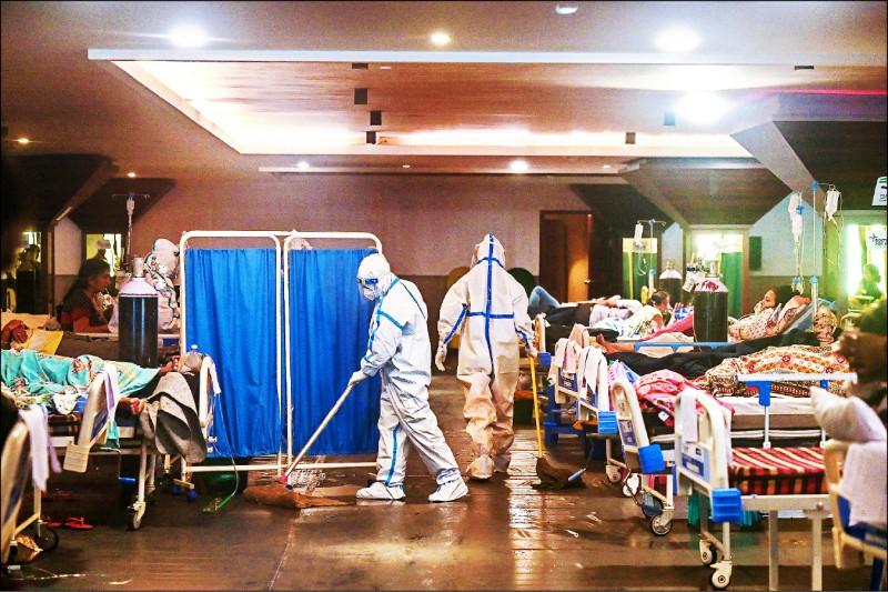 首都新德里一家醫院的衛生人員穿戴完整防護裝備,清洗收容病患的診間。(法新社)