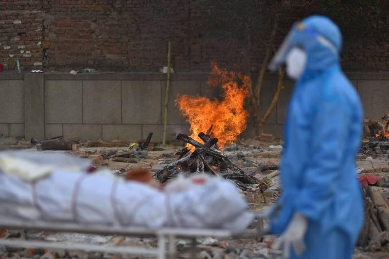 印度盡期面臨疫情大爆發,單日新增確診病例突破40萬。圖為火葬工作人員搬運遺體。(歐新社)