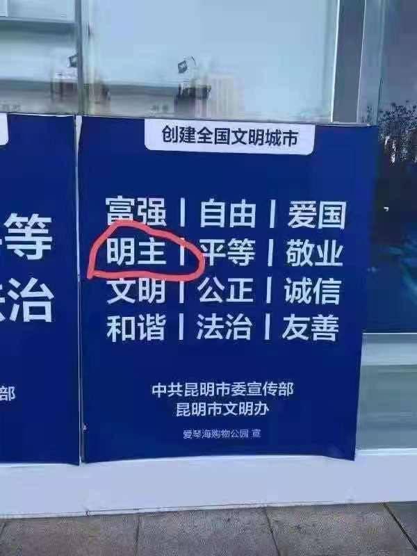 網友上傳中國雲南昆明市市委宣傳部設立的告示牌,其中「富強」、「自由」等標語中,卻夾雜了「明主」一詞,讓網友一時摸不著頭緒,仔細一想才想到原來是指「民主」。(擷取自推特)