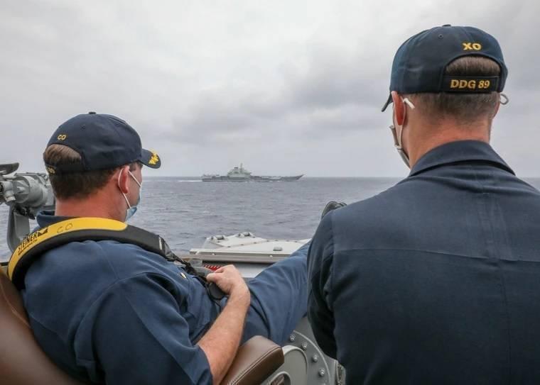 中國遼寧號航空母艦4月浩浩蕩蕩穿越宮古水道進入太平洋,卻被美軍發布這張照片打臉,柏克級驅逐艦馬斯廷號艦長(左)「翹腳」盯著不遠處的遼寧號,引爆話題。(資料照,翻攝美國海軍官網)