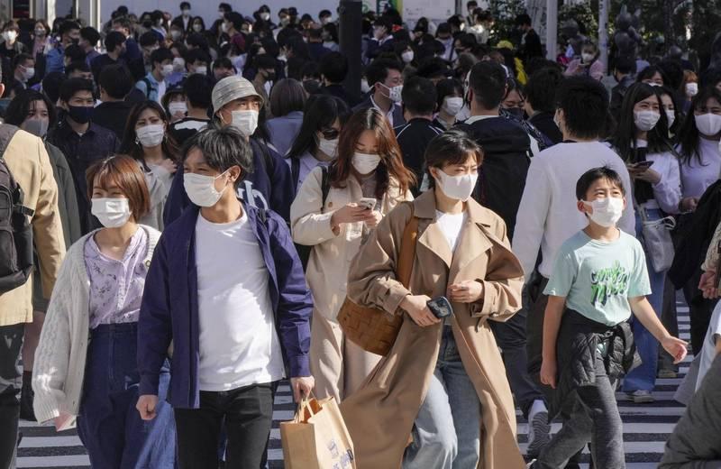 日本厚生勞動省統計,今天境內武漢肺炎重症患者達1084人,創新高紀錄,且是連續兩天創新高。圖為人們戴著防護口罩走在東京人行穿越道上。(歐新社)