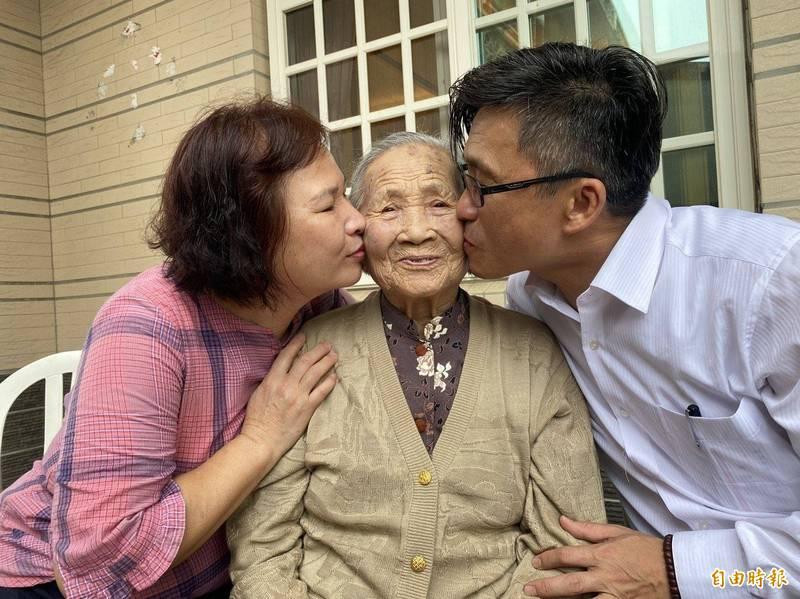 金門100歲人瑞黃為治(中)獲海軍艦隊指揮部選為模範母親,開心接受女兒陳雪玉(左)、女婿黃聿標(右)獻吻。(記者吳正庭攝)
