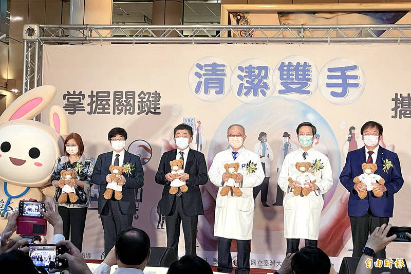 Minister of Health and Welfare Chen Shih-chung, third left, and other officials hold teddy bears at a news conference in Taipei yesterday. Photo: Chiu Chih-jou, Taipei Times