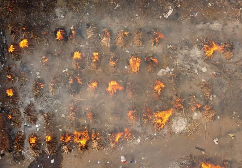 印度武漢肺炎疫情急轉直下,已連續12天單日確診超過30萬例,火葬場無法負荷的遺體直接在空地集體火化。(路透)