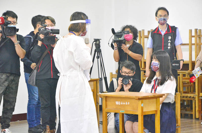 An exam proctor wearing personal protective equipment supervises a student of Haishan High School in a New Taipei City Education Department drill yesterday simulating what to do during an examination if a student is found to have a fever. Photo: CNA