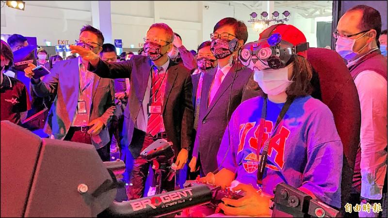 智崴董事長歐陽志宏(左二)向市長陳其邁介紹放視大賞展覽的MR體感賽車。(記者許麗娟攝)