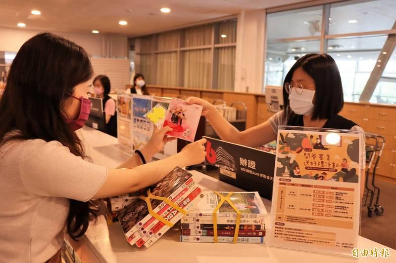 民眾在高市圖各分館,借閱滿冊即可選擇眼罩、面膜、衛生紙、便利貼、商品卡等禮品。(記者許麗娟攝)
