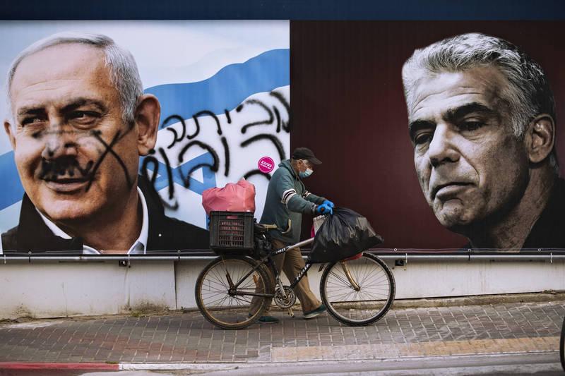 以色列街頭上,第1大黨聯合黨黨魁、現任總理納坦雅胡(左),與3月大選後成為第2大黨的未來黨領導人拉皮德(右)競選廣告看板並列。納坦雅胡肖像上被塗寫上希伯來語「回家」。由於納坦雅胡未能在期限內組成新政府,以色列總統李佛林今天欽點拉皮德籌組新政府。此舉可能導致納坦雅胡時代結束。(美聯社)