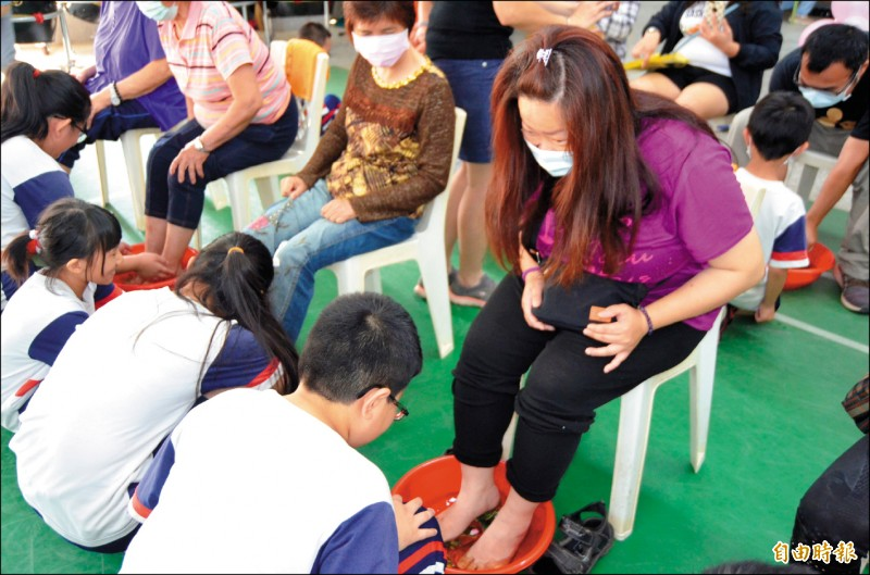 育仁國小學童的媽媽享受小朋友洗腳服務。(記者林國賢攝)