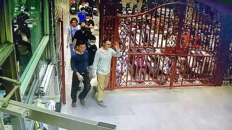 警方搜索時,會同阮哲夫(圖中,揮手者)進入住處。(民眾提供)