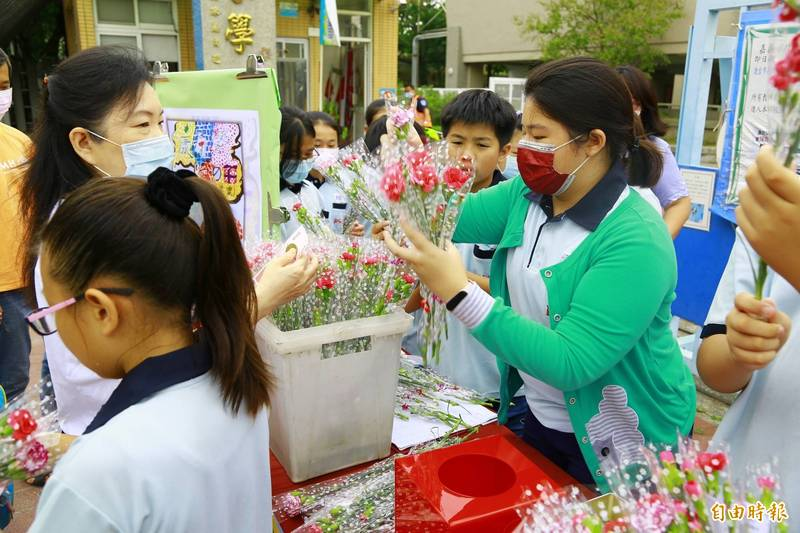嘉義市北園國小學生與嘉義市農會合作販售康乃馨。(記者林宜樟攝)