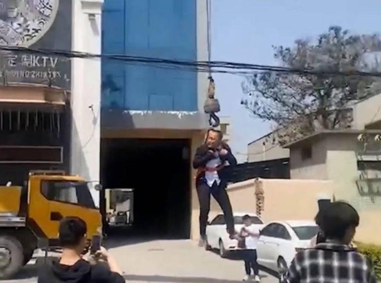 中國河南一名新郎,被朋友「鬧洞房」給五花大綁掛在吊車上。(圖翻攝自微博)
