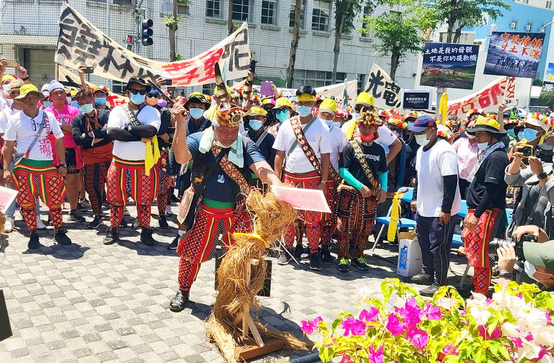 A Puyuma elder cuts down a straw man at a protest against a solar power plant project outside the Taitung County Government building yesterday. Photo: CNA